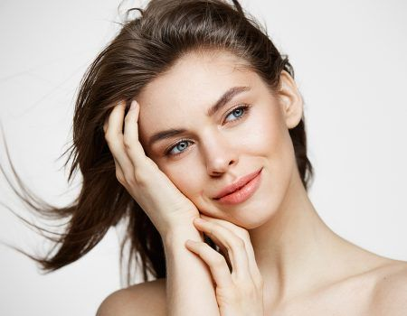 Beautiful naked young girl with perfect clean skin smiling touching hair over white wall. Facial treatment. Copy space.